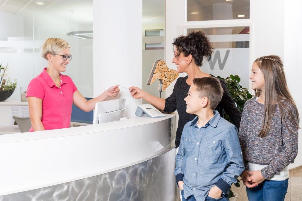 Mutter mit Kindern beim Zahnarzt, gibt Versichertenkarte ab